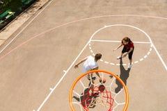 Couples jouant le basket-ball sur la cour extérieure Image stock