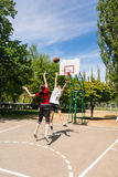 Couples jouant le basket-ball sur la cour extérieure Images libres de droits