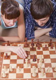 Couples jouant le jeu d'échecs ensemble Photos stock
