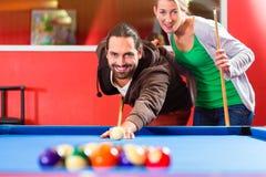 Couples jouant le jeu de billard de piscine Photographie stock
