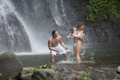 Couples jouant sous des cascades à écriture ligne par ligne Photos libres de droits