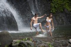 Couples jouant sous des cascades à écriture ligne par ligne Photographie stock