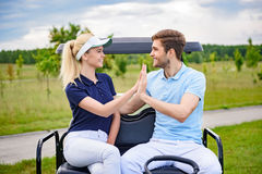 Couples jouants au golf attrayants se donnant salut-cinq Image libre de droits