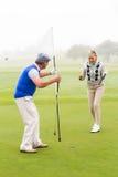 Couples jouants au golf encourageant sur le putting green Photographie stock