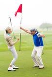 Couples jouants au golf encourageants Images libres de droits