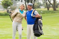 Couples jouants au golf marchant sur le putting green Image libre de droits