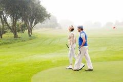 Couples jouants au golf marchant sur le putting green Photos libres de droits