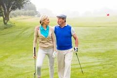 Couples jouants au golf marchant sur le putting green Photographie stock libre de droits