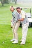 Couples jouants au golf mettant la boule souriant ensemble à l'appareil-photo Photo stock