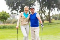 Couples jouants au golf souriant à l'appareil-photo sur le putting green Photos libres de droits
