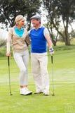 Couples jouants au golf souriant à l'un l'autre sur le putting green Image libre de droits