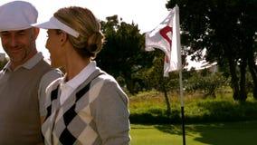 Couples jouants au golf souriant au dix-huitième trou sur le terrain de golf banque de vidéos