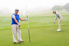 Couples jouants au golf sur le terrain de golf Image stock