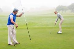 Couples jouants au golf sur le terrain de golf Images libres de droits