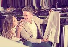 Couples joyeux choisissant de nouveaux pantalons dans le magasin de tissus Photo stock