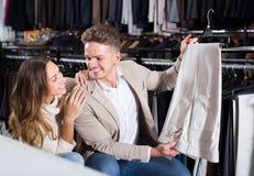Couples joyeux choisissant de nouveaux pantalons dans le magasin de tissus Photographie stock libre de droits