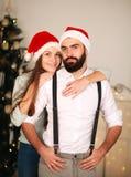 Couples joyeux dans des chapeaux rouges sur le fond de l'arbre de Noël Image stock