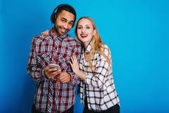 Couples joyeux de portrait de jeune femme attarctive avec de longs cheveux blonds ayant l'amusement ainsi que l'écoute belle de t photos stock