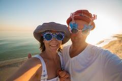Couples joyeux des voyageurs dans des lunettes de soleil drôles prenant le selfie Photos stock