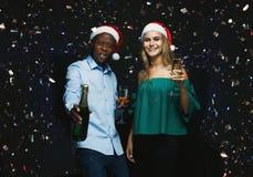 Couples joyeux félicitant sur Noël avec le champagne au fond noir Photos libres de droits