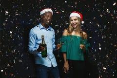 Couples joyeux félicitant sur Noël avec le champagne au fond noir Photographie stock libre de droits