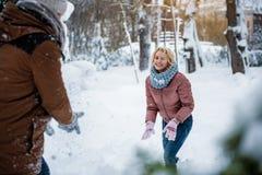Couples joyeux jouant des boules de neige dans la forêt Photo stock