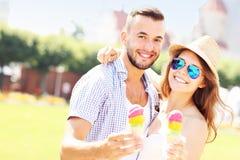 Couples joyeux mangeant des cornets de crème glacée Images stock