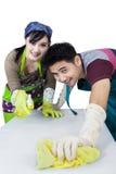 Couples joyeux nettoyant une table Images stock