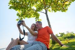 Couples joyeux prenant le selfie tout en se reposant sur un pré vert Image stock