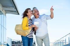 Couples joyeux regardant loin contre le ciel Photographie stock libre de droits