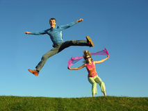 Couples jump on grass. Blue sky stock photos