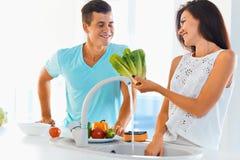 Couples lavant les légumes organiques ensemble Image libre de droits
