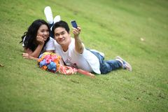 Couples laying on grass and taking self portrait Royalty Free Stock Photos