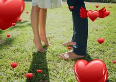 Couples legs in garden with digitally generated red valentines hearts Royalty Free Stock Photo