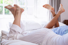 Couples legs lying on bed Royalty Free Stock Image