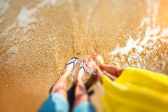 Couples legs in slippers on the beach Stock Photography
