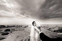 Couples les ?pousant ?l?gants se tenant sur le bord de mer Les nouveaux mari?s marchent par la mer Rebecca 36 photo libre de droits