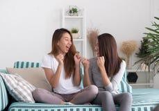Couples lesbiens de lgbt de l'Asie tenant l'exposition de TV et le che de observation à distance Image libre de droits