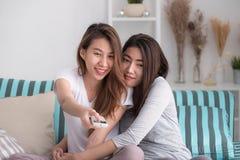 Couples lesbiens de lgbt de l'Asie tenant le togethe de observation à distance d'exposition de TV Images libres de droits