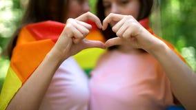 Couples lesbiens enveloppés dans le drapeau d'arc-en-ciel, démonstration libre de l'amour, droites de lgbt photo stock
