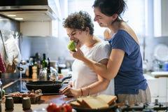 Couples lesbiens faisant cuire dans la cuisine ensemble photo stock