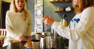 Couples lesbiens préparant le café et à l'aide du comprimé numérique dans la cuisine 4k banque de vidéos