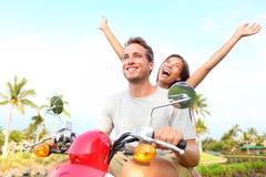 Couples libres heureux de liberté conduisant le scooter Photos stock