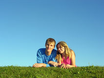 Couples lie on grass. Blue sky stock photo