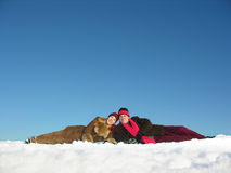 Couples lies on snow. Blue sky stock images