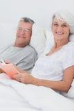 Couples lisant ensemble dans le lit Photos libres de droits