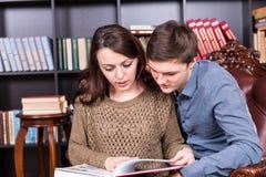 Couples lisant un livre sur une chaise ainsi fermée Image stock