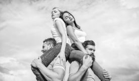 Couples in love having fun. Men carry girlfriends on shoulders. Summer vacation and fun. Couples on double date. Inviting another couple to join. Twice fun on stock photography