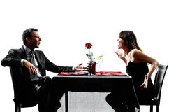 Couples lovers dating dinner  dispute arguing silhouettes Royalty Free Stock Images