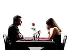 Couples lovers dating dinner  dispute separation silhouettes. Couples lovers dinning dispute separation in silhouettes on white background Royalty Free Stock Image